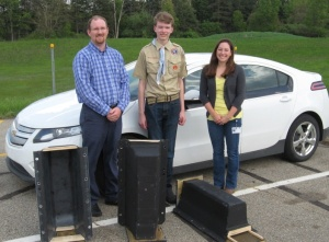Rich Castle with Consumers Energy, Eagle Scout Matthew Netherland, and Emily McDonald with GM stand next to bat houses made with Chevrolet Volt battery cases.