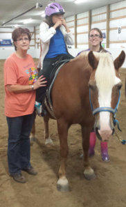 Debra and her daughter volunteering at Therapeutic Riding Inc.
