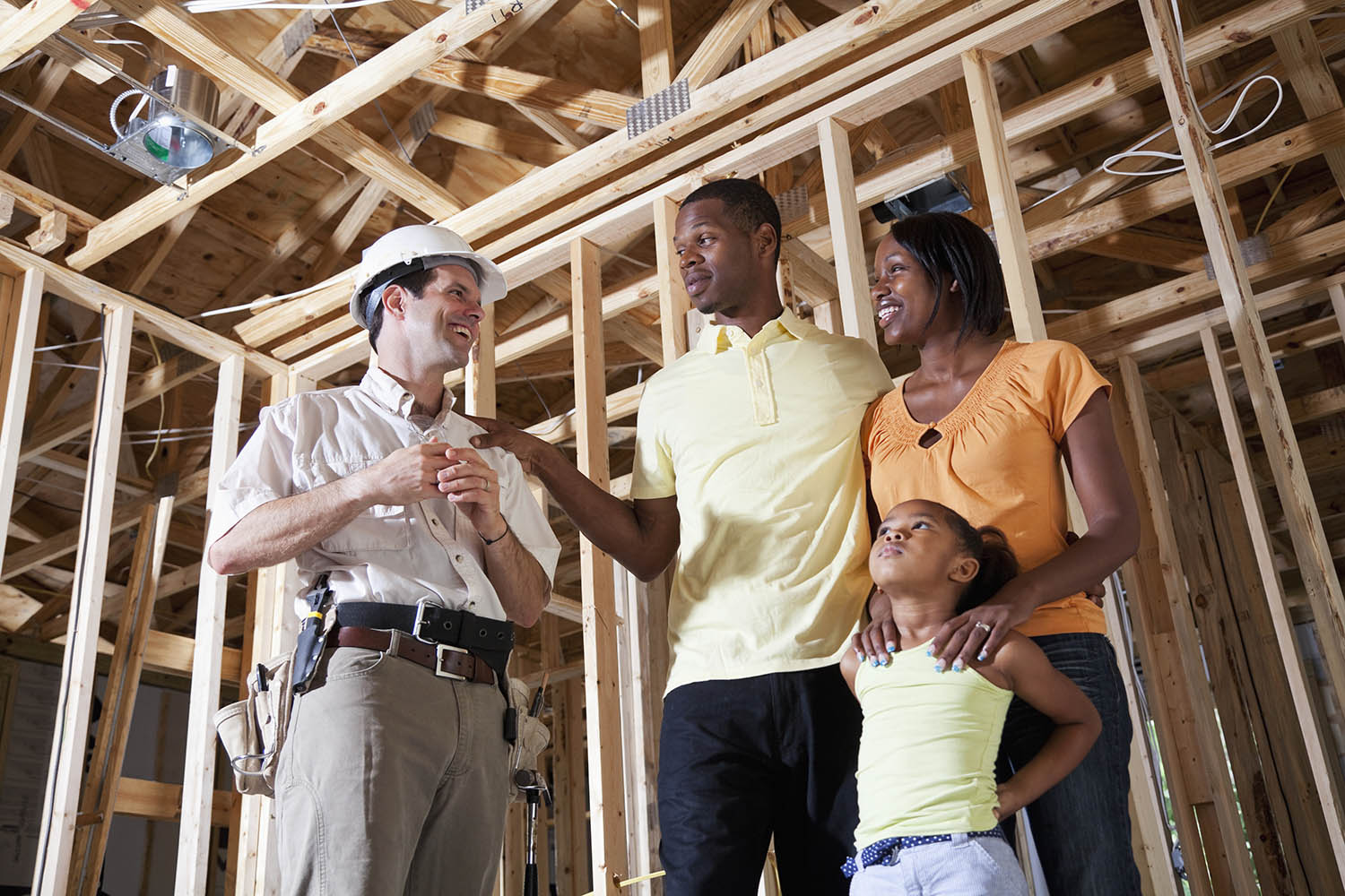 African American family standing in house under construction talking with builder.